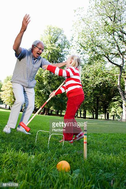 Girl and senior man playing croquet in the park Sweden.