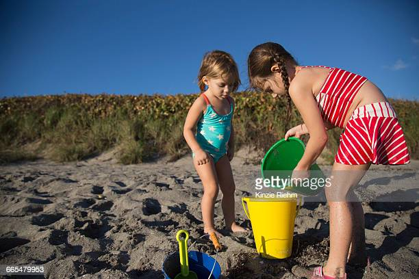 girl and sister playing with toy buckets on beach, blowing rocks preserve, jupiter island, florida, usa - jupiter island stock photos and pictures