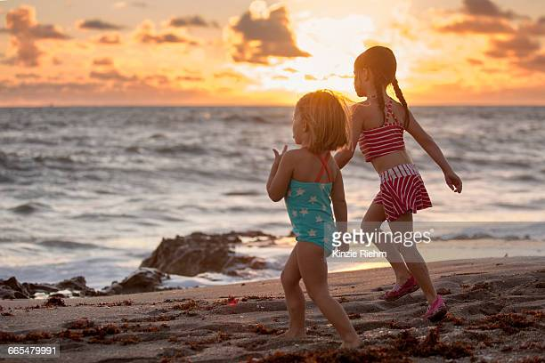 Girl and sister running on beach at sunrise, Blowing Rocks Preserve, Jupiter Island, Florida, USA