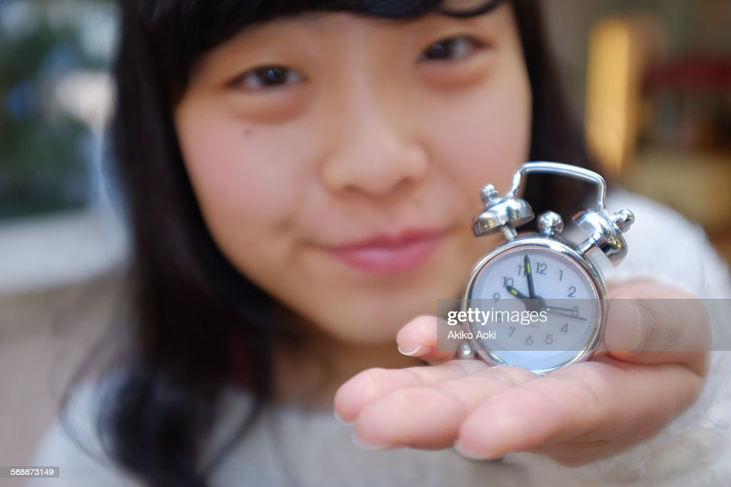 Girl and small alarm clock on her hand. : Stock Photo