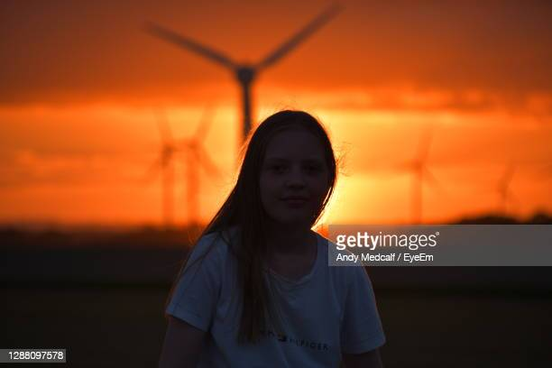girl and sunset over the holderness fields at rimswell east yorkshire uk wind turbine in background - rural scene stock pictures, royalty-free photos & images