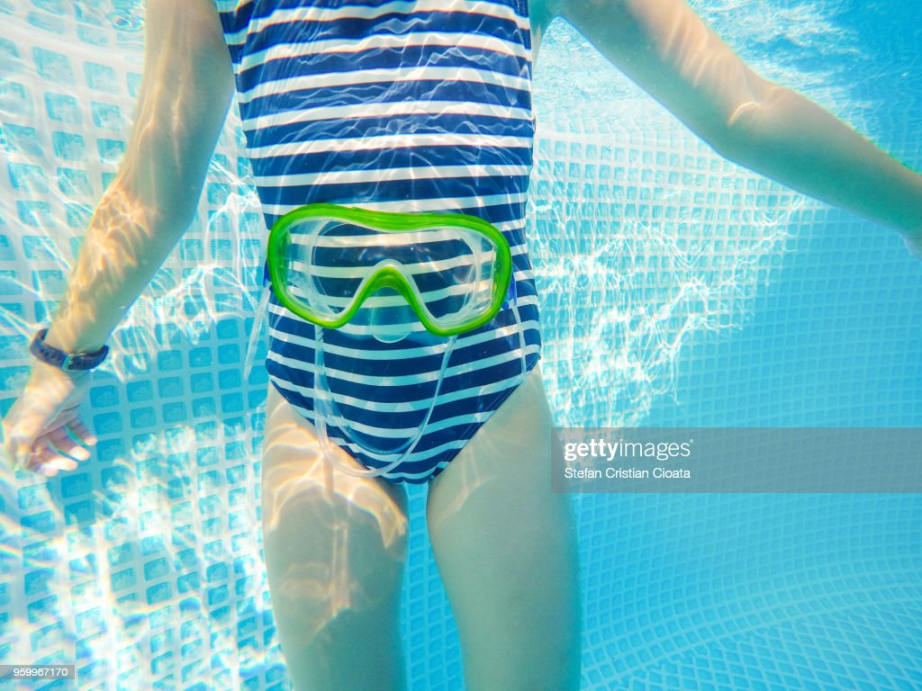 Girl and swimming goggles underwater : Stock-Foto