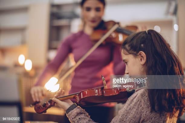 Girl and teacher playing violin