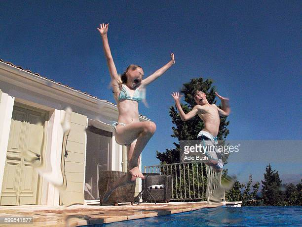 Girl and teenage brother jumping into apartment swimming pool