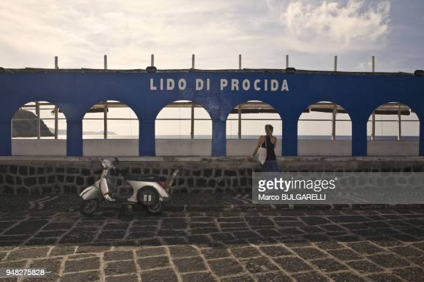 A girl and the famous motorbike Vespa in Marina di Chiaiolella on June 11 2012 in Procida Italy
