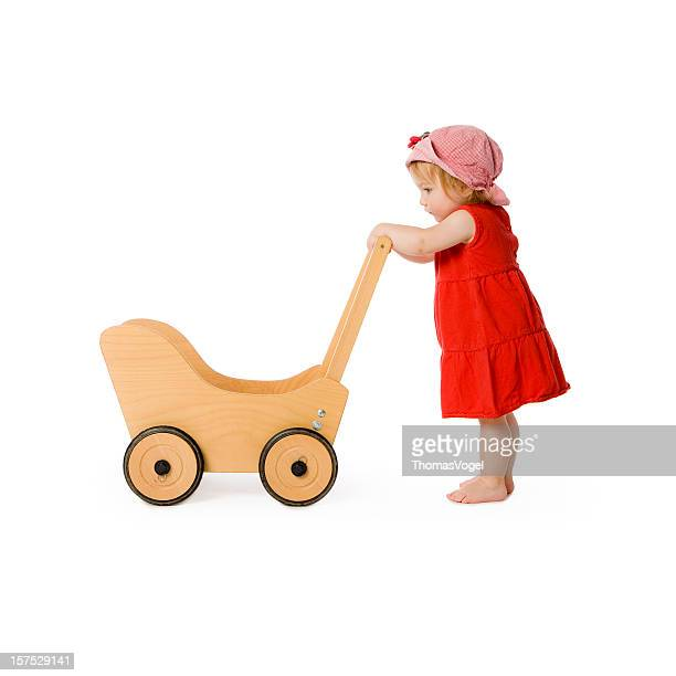 girl and toy wagon. Baby Carriage Toddler Child Pushing