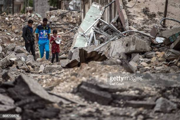 A girl and two boys walk to a Shia volunteer food distribution point during fighting against Islamic State in west Mosul on April 12 2017 in Mosul...