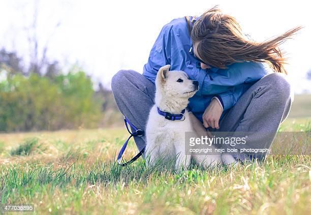 girl and white puppy in nature - un animal fotografías e imágenes de stock