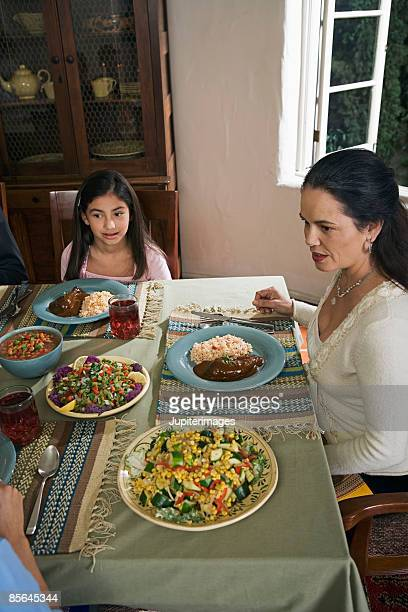 girl and woman at dining table - mole sauce stock pictures, royalty-free photos & images