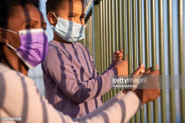 girl and woman in face masks looking away through the fence bars. coronavirus pandemic concept. - child behind bars stock pictures, royalty-free photos & images