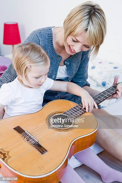 Girl and woman playing with a guitar