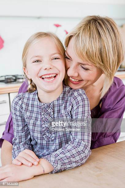 Girl and woman sitting at table hugging