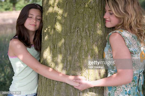 Girl (12-13 years) and young woman holding hands, hugging tree trunk
