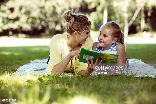 girl and young woman with book lying on blanket in a park - aunt stock pictures, royalty-free photos & images