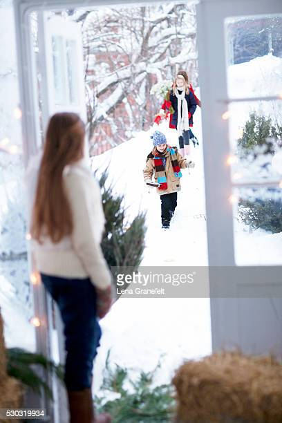 Girl answering door to guests with flowers in snow