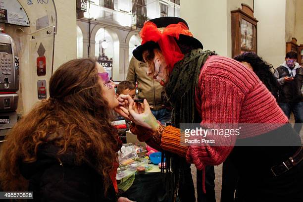 Girl applies make-up on another girl for Halloween.