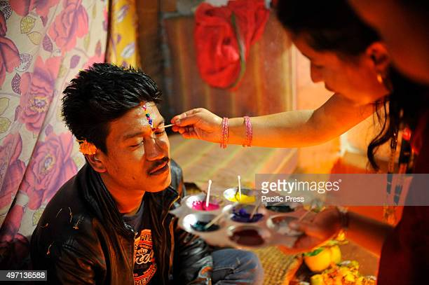NAGAUN KIRTIPUR KATHMANDU NEPAL KATHMANDU NP NEPAL A girl applies seven layers of colorful vermilion powder on his brothers' forehead The Bhai Tika...
