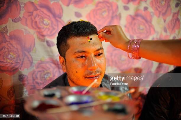 NAGAUN KIRTIPUR KATHMANDU NEPAL KATHMANDU NP NEPAL A girl applies seven layers of colorful vermilion powder on his brothers' forehead The Bhai Tika...