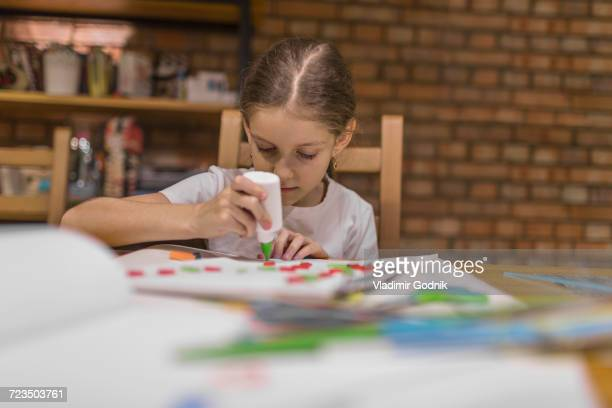Girl applying glue on paper while making craft product at home