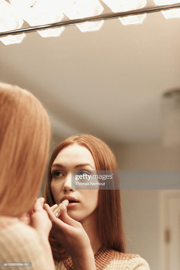 Girl (14-15) applying lipstick, looking in mirror : Foto stock