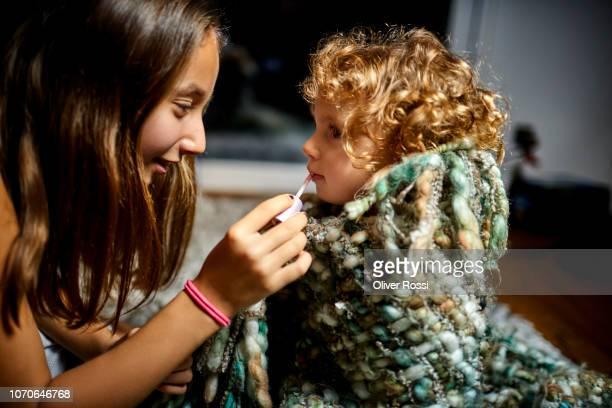 Girl applying lipstick on younger sister's lips