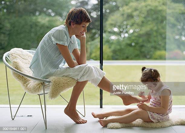 Girl (3-5) applying nail varnish to mother's toenails