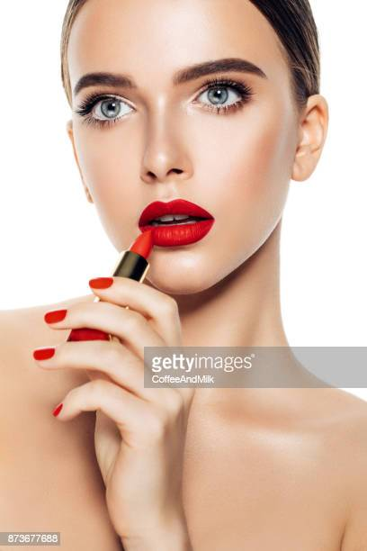 Girl applying red lipstick on her lips