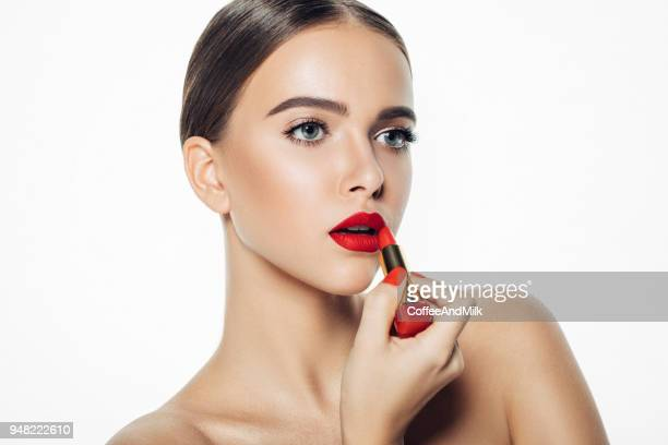 girl applying red lipstick on her lips - red lipstick stock pictures, royalty-free photos & images