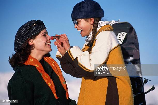 Girl (9-11) applying sun-block to mother's face in snowscape