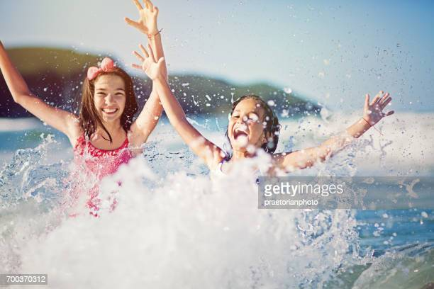 Girl are jumping and playing in the ocean in the big waves