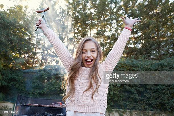 girl arms raised holding sausage on fork looking at camera smiling - snag tree stock pictures, royalty-free photos & images