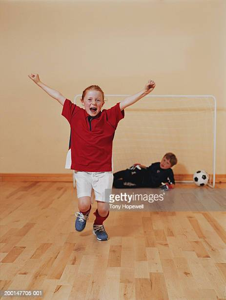 Girl (6-8), arms raised, infront of boy (8-10) defending football goal