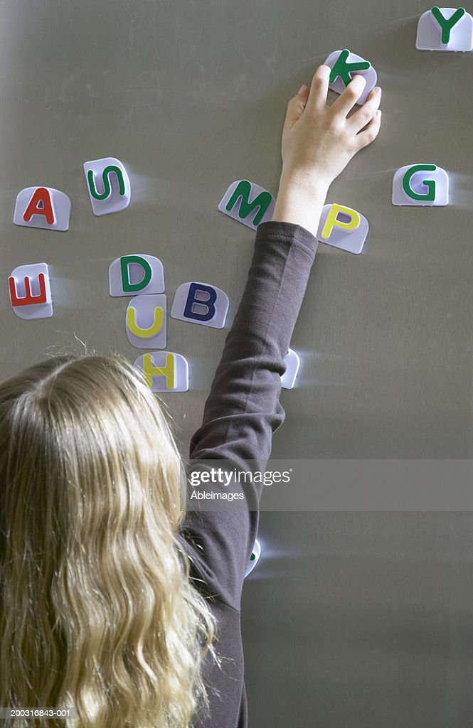 Girl (5-7) arranging magnetic letters on fridge, rear view : Stock Photo