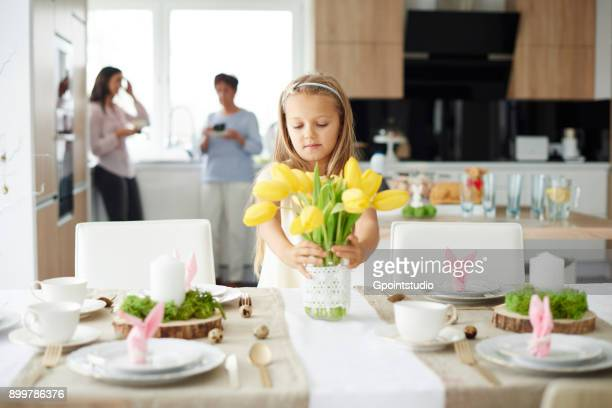 Girl arranging yellow tulips at easter dining table