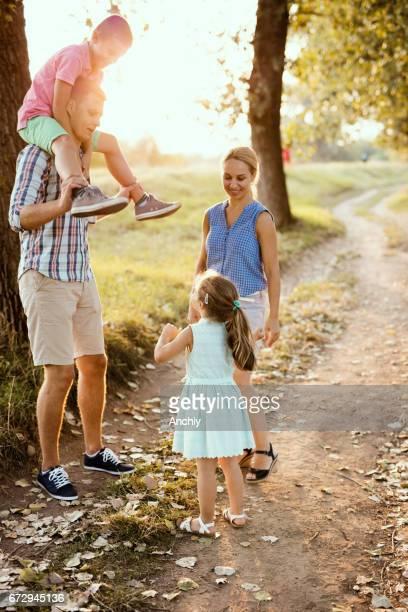 Meisje vraagt vader wanneer is het haar beurt om te rijden op zijn schouders. Familie spelen op het platteland in de herfst.