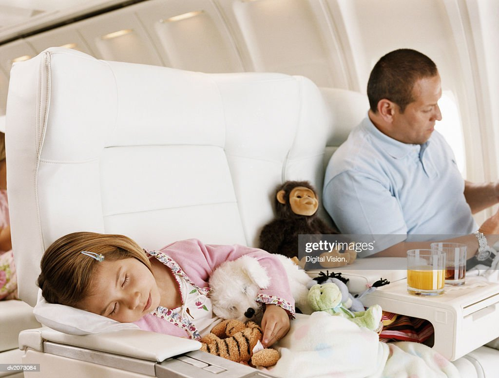Girl Asleep and Her Father Sitting Beside Her in an Aircraft Cabin : Stock Photo