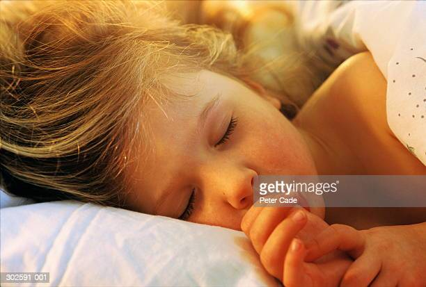 Girl (2-4) asleep in bed, close-up