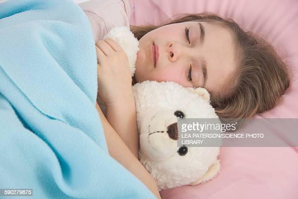 Girl asleep in bed holding teddy bear