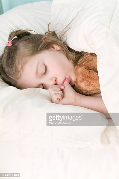 Girl (5-7) asleep in bed sucking her thumb