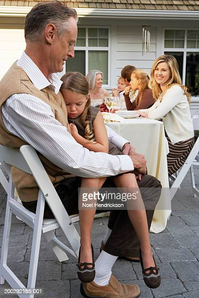 girl (5-7 years) asleep on grandfather's lap at family meal on patio - 55 59 years stock pictures, royalty-free photos & images
