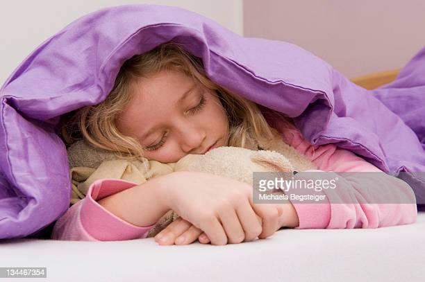 Girl asleep under bedspread