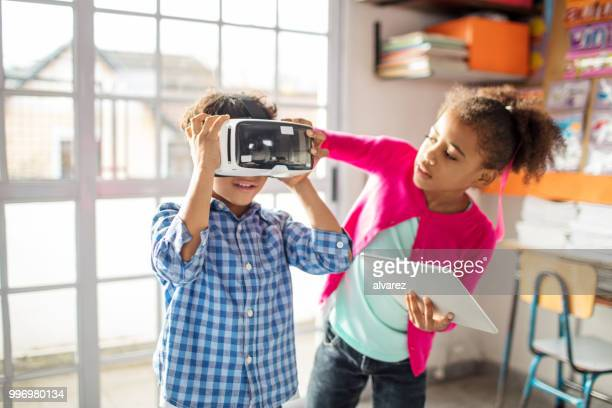 Girl assisting boy to wear VR headset in class