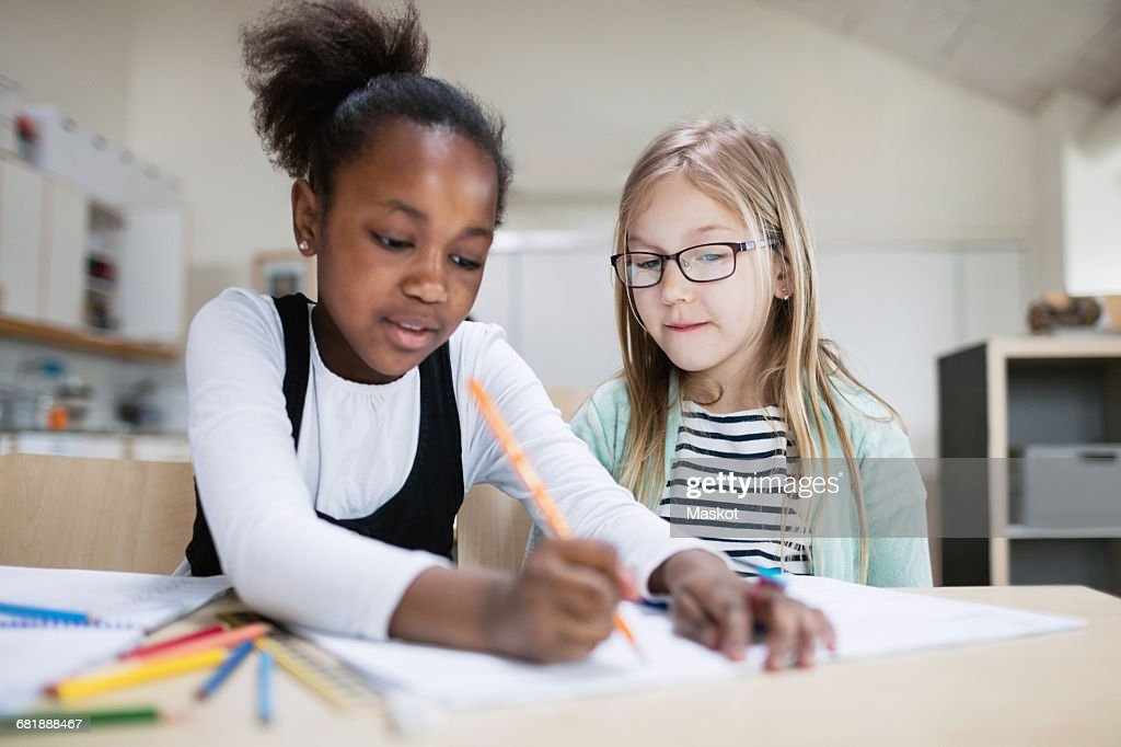 Girl assisting friend while studying in classroom at school : Stock Photo