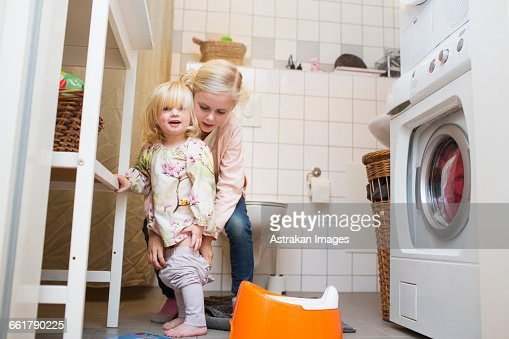 Girl Assisting Sister To Wear Pants At Bathroom Stock Photo Getty Images