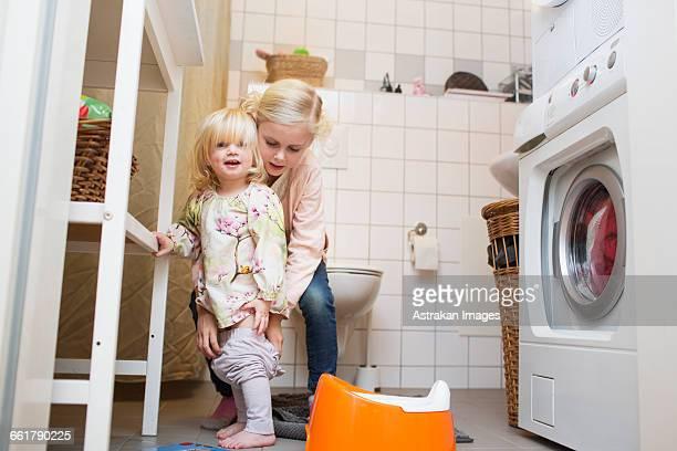 Girl assisting sister to wear pants at bathroom