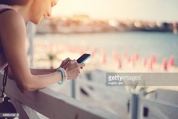 Girl at a veranda text messaging on the phone