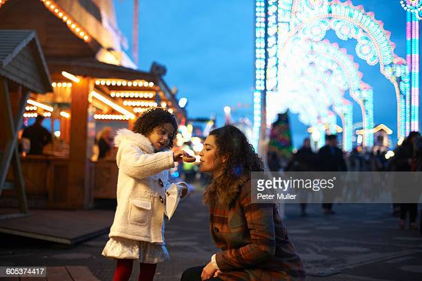 Girl at amusement park feeding mother doughnuts