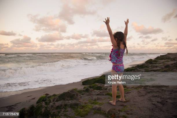 girl at beach arms raised looking away at view, blowing rocks preserve, jupiter, florida, usa - jupiter island stock photos and pictures