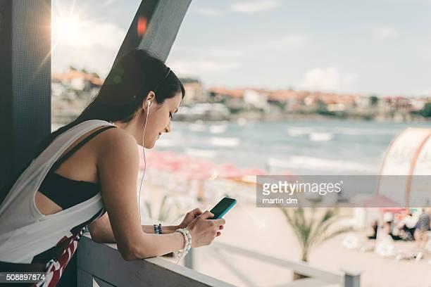 Girl at beach veranda using smartphone