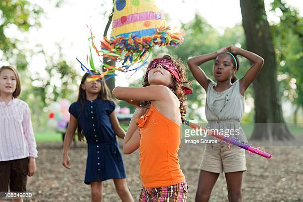 Girl at birthday party hitting pinata